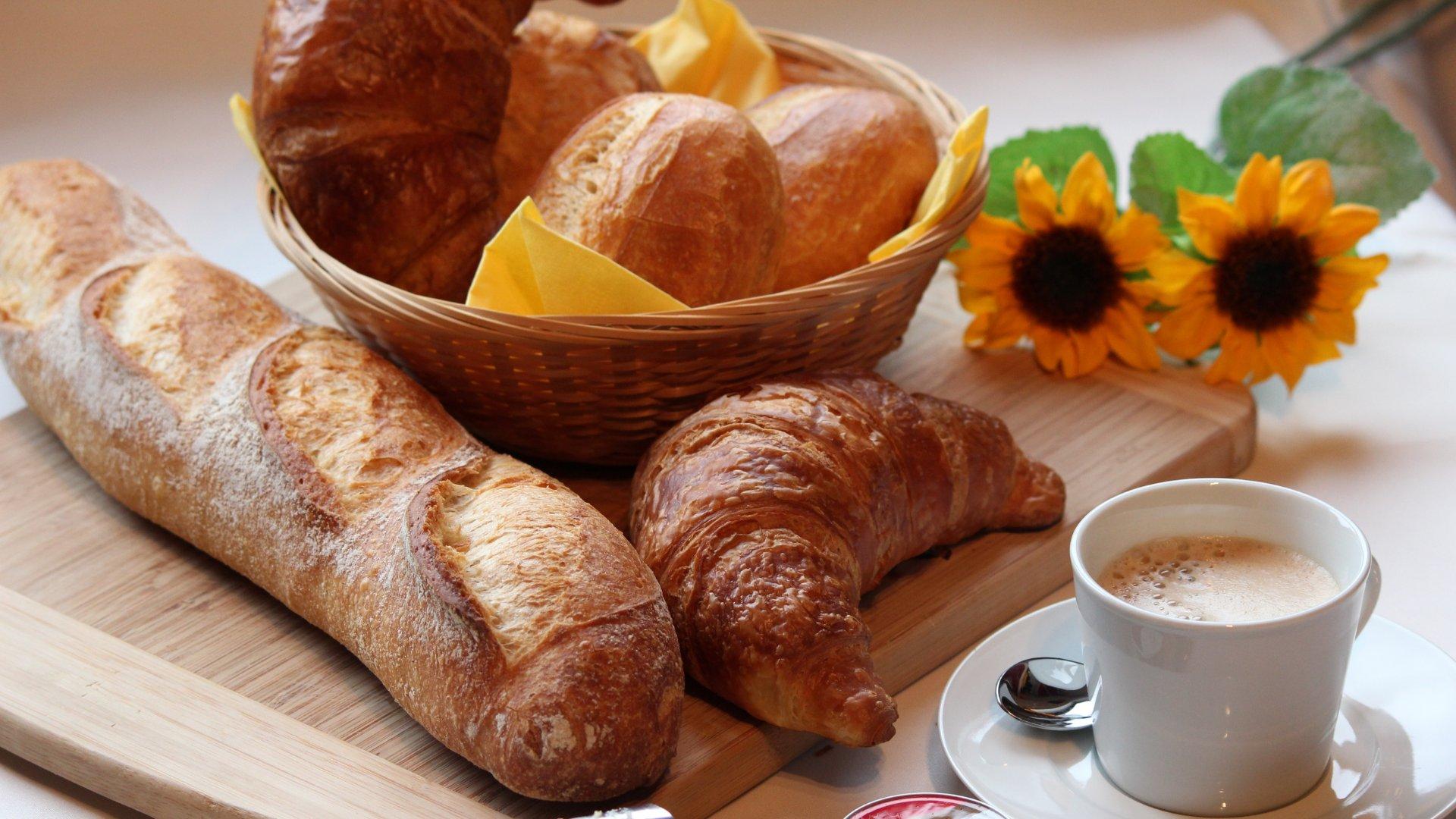 Prato de café da manhã com pães, xícara de café e flor de girassol