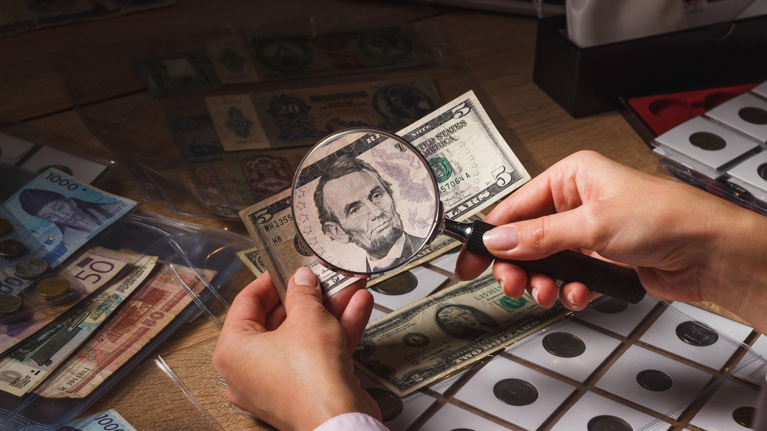 Numismata apontando uma lupa sobre uma nota de dólar.