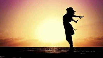 Mulher de pé em uma prancha de wakeboard, com os braços esticados para trás..
