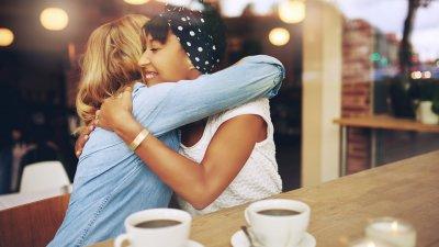 Duas mulheres em um café se abraçando.