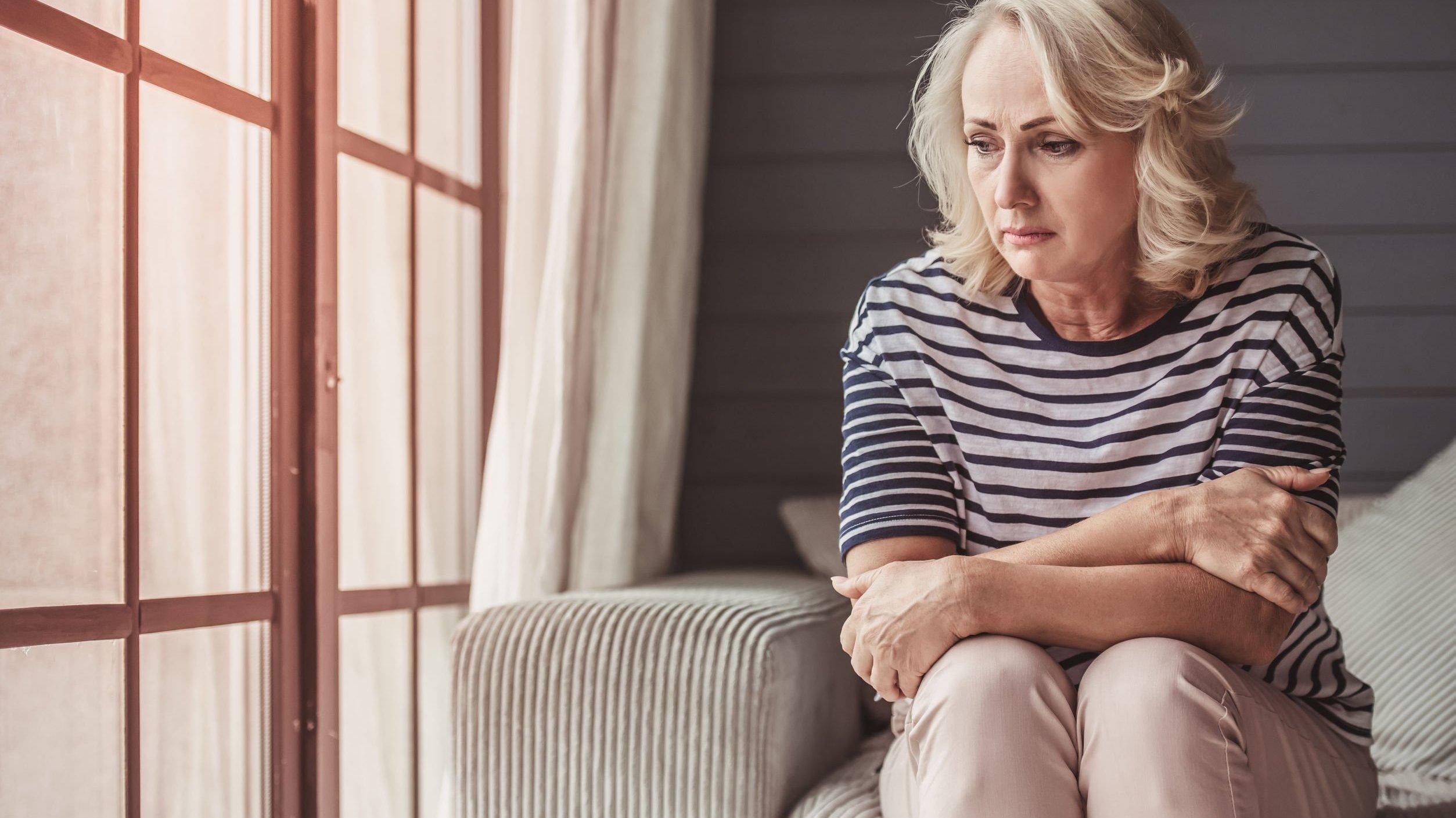 Senhora com o olhar triste sentada em um sofá