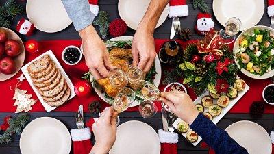 Pessoas brindando sobre a mesa de ceia de Natal.