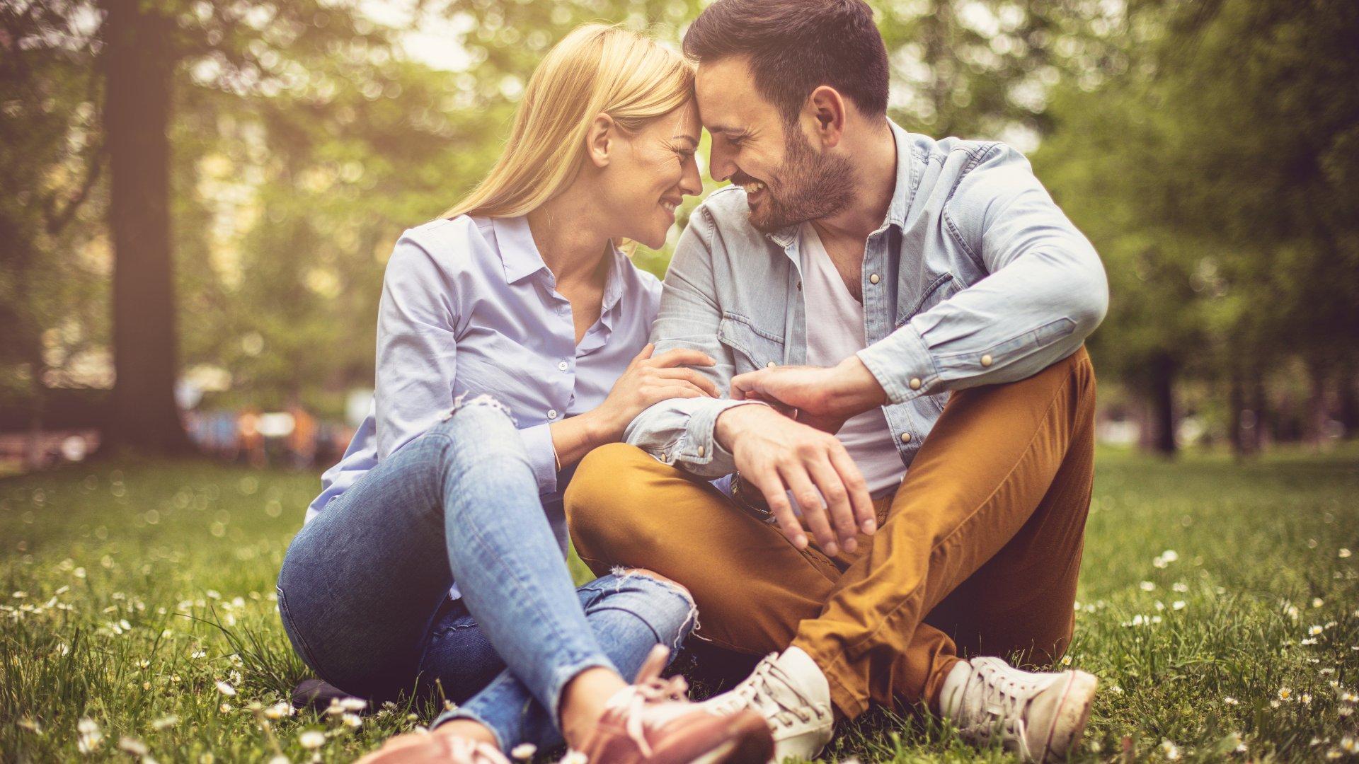 Casal sentado na grama se olhando enquanto sorriem