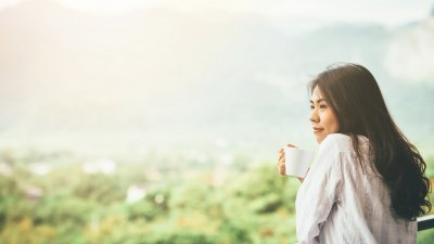 Mulher tomando café na varanda.