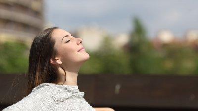 Mulher com os olhos fechados sentindo o vento