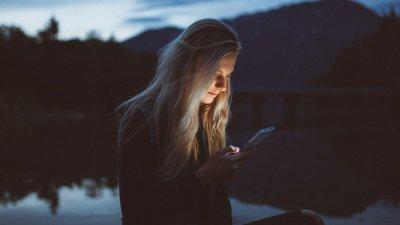 Mulher sentada próxima a um lago no começo da noite, mexendo no celular.