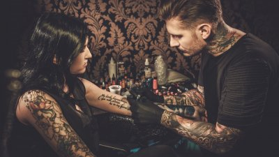 Homem e mulher cobertos por tatuagens. O homem está tatuando o braço esquerdo da mulher.