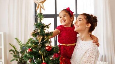 Mulher segurando menina no colo em frente de árvore de Natal. A menina está colocando uma estrela no topo da árvore.