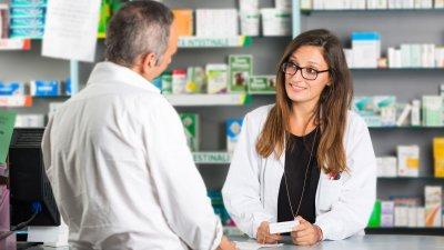 Farmacêutica oferecendo medicamento para cliente.