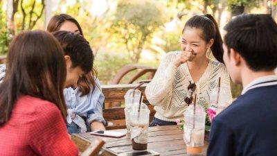 Jovens rindo em mesa de piquenique