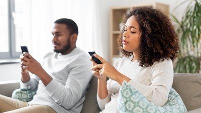 Homem e mulher sentados em sofá, ambos mexendo em seus celulares.