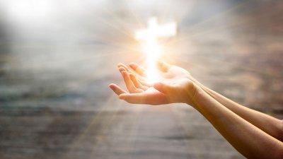 Mãos segurando uma cruz brilhante.