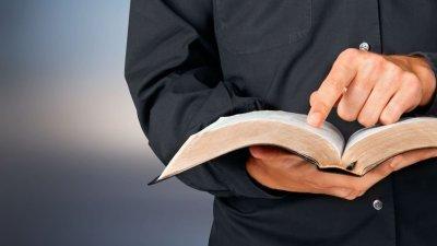 Perfil de pastor segurando uma bíblia e apontando o dedo indicador para frente.