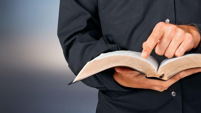 Pastor segurando uma bíblia, enquanto com um dos dedos acompanha a leitura da mesma