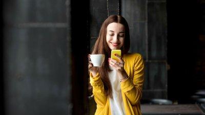 Mulher olhando para celular segurando xícara na outra mão sorrindo