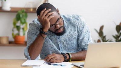 Homem apoiando na mesa do escritório de cabeça baixa