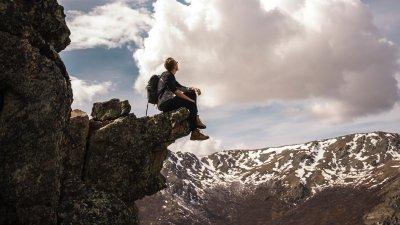 Homem sentado na beira da montanha olhando para o céu