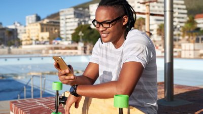 Homem sentado com um skate no colo e usando seu celular com a mão direita.