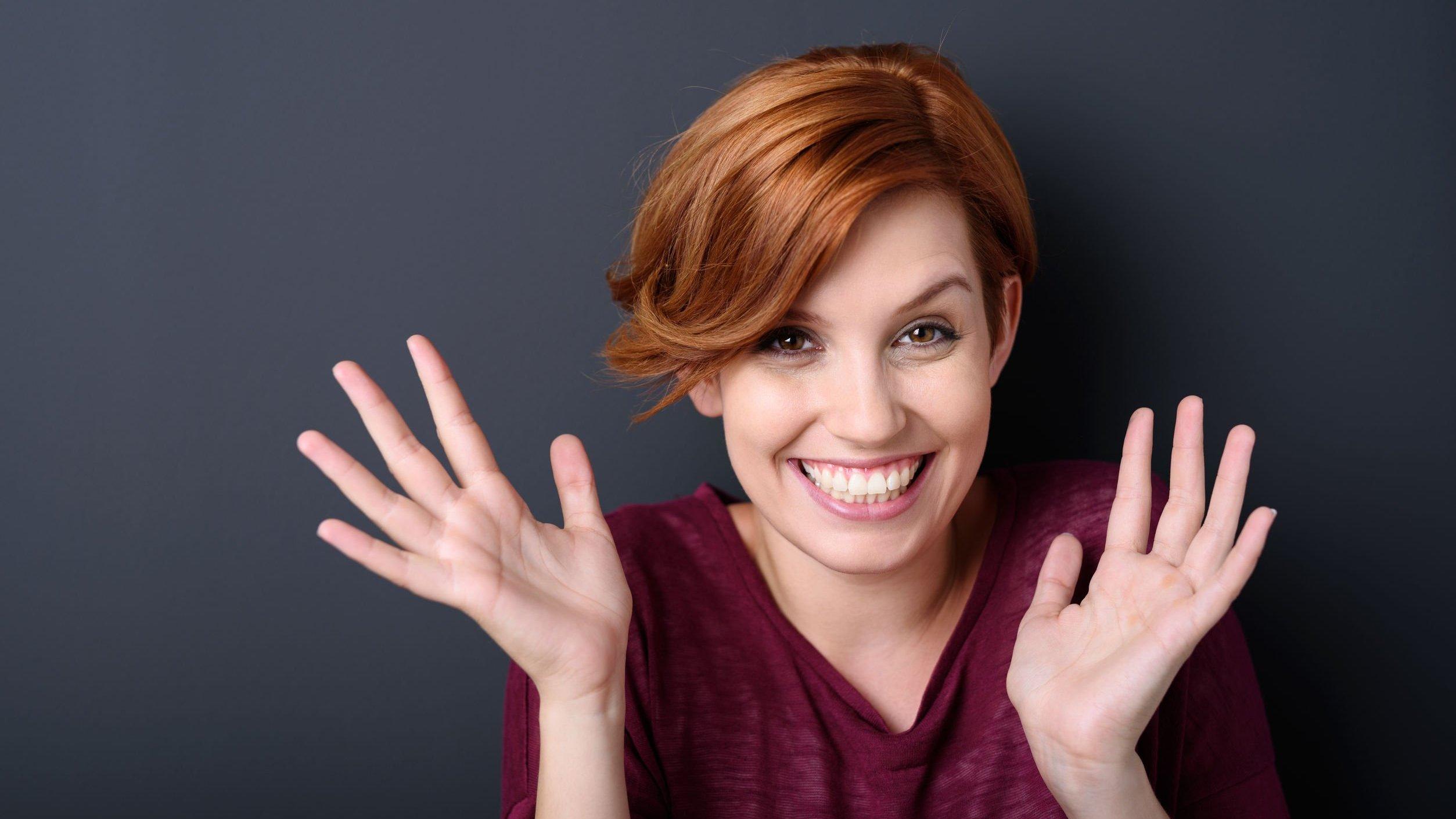 Mulher sorrindo com as mãos abertas em direção ao rosto