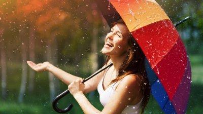 Foto de mulher feliz com guarda chuva na chuva