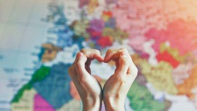 Mãos fazendo forma de coração em frente de mapa mundi