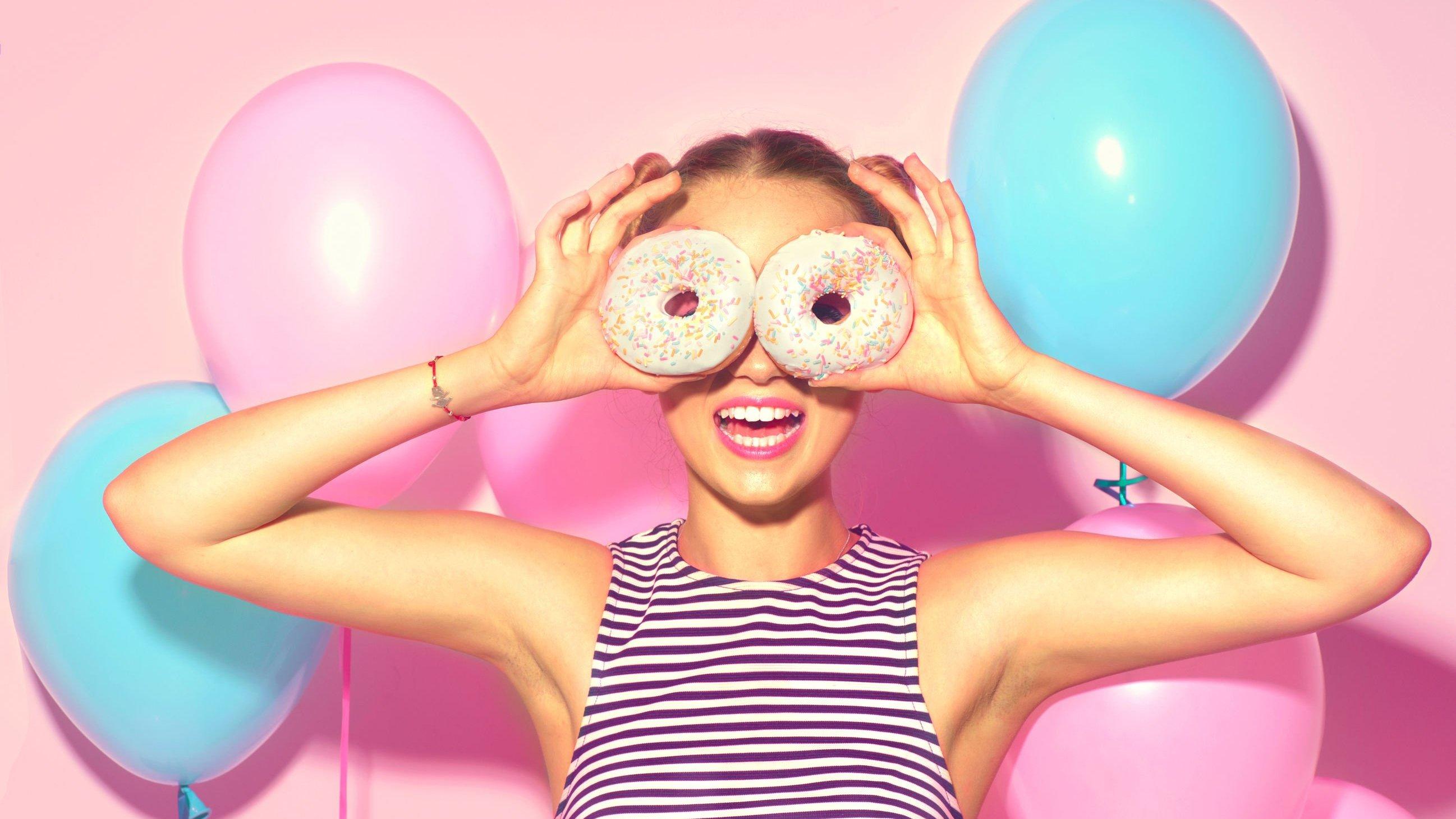 Foto de mulher segurando rosquinhas na frente do rosto