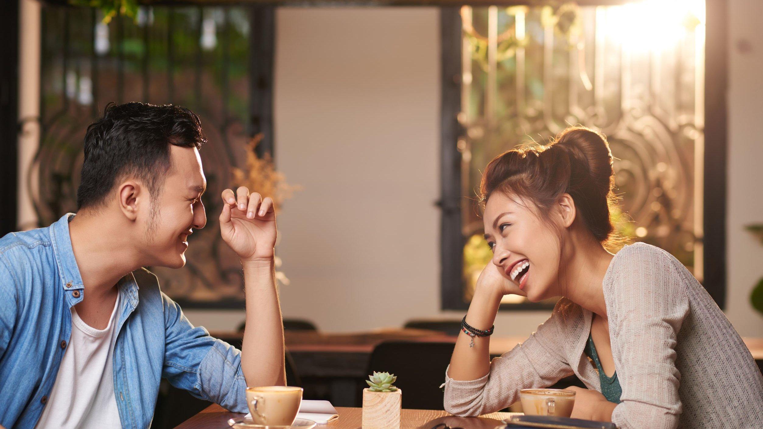 Foto de homem e mulher sentados conversando e sorrindo