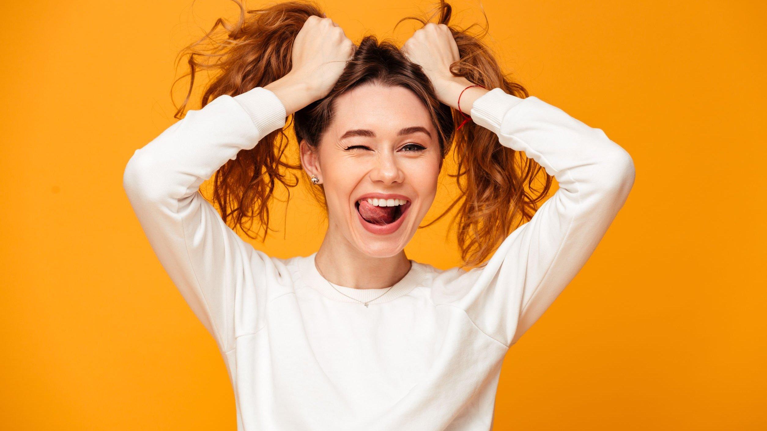 Mulher segurando o cabelo e sorrindo
