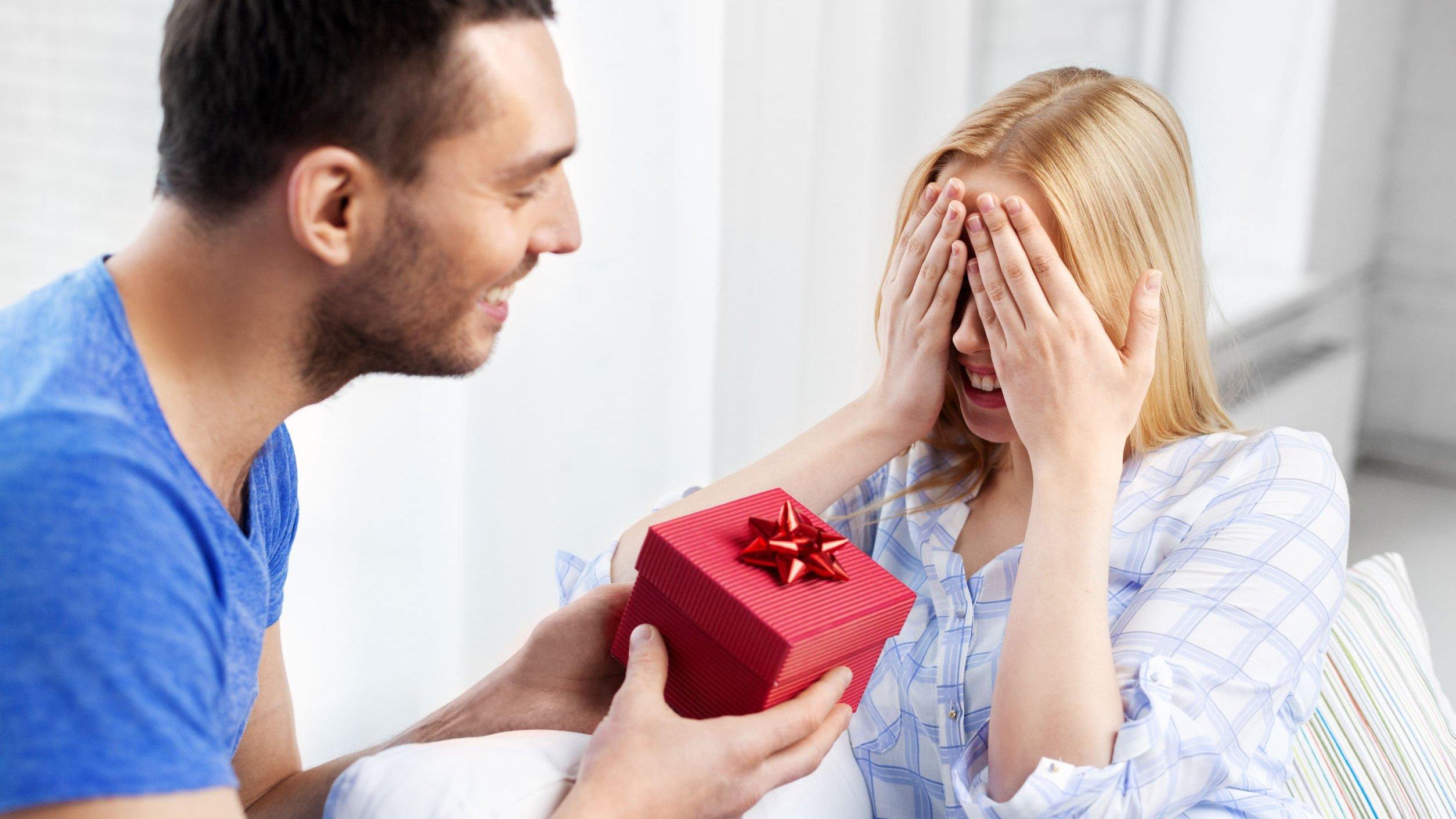 Homem entrega caixa de presente para mulher que cobre os olhos com as mãos.