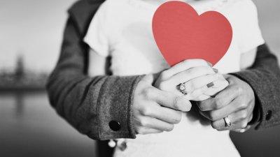 Foto de casal juntos segurando um coração de papel
