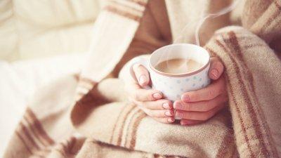 Pessoa com coberta marrom segura xícara com café com leite quente.