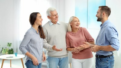 Casal conversa com seus sogros em uma sala de estar.