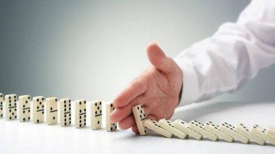 Pedras de dominó caindo em sequência com mão interferindo na  queda