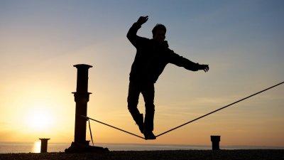 Silhueta de pessoa se equilibrando em corda bamba