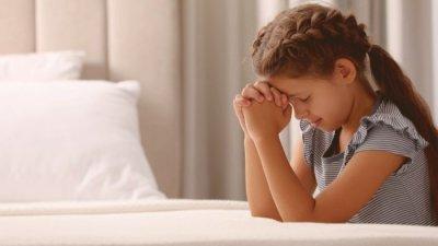 Menina loira ajoelhada ao lado da cama, rezando.