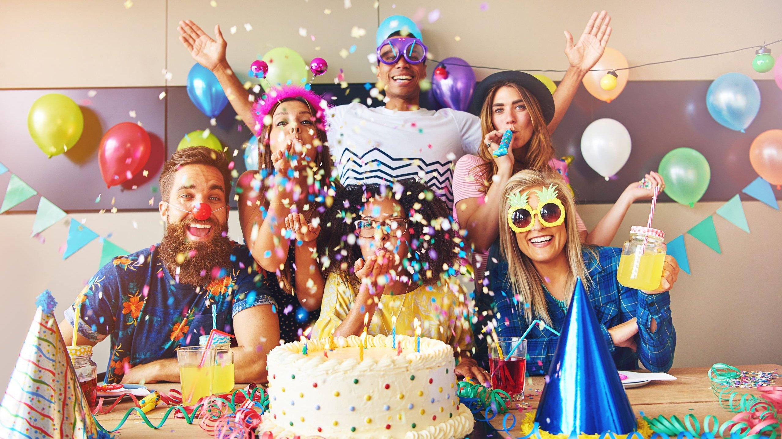 Grupo com seis pessoas usando máscaras e acessórios de festa comemora atrás de um bolo de aniversário.