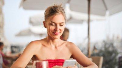 Mulher loira usando o celular em um restaurante ao ar livre.