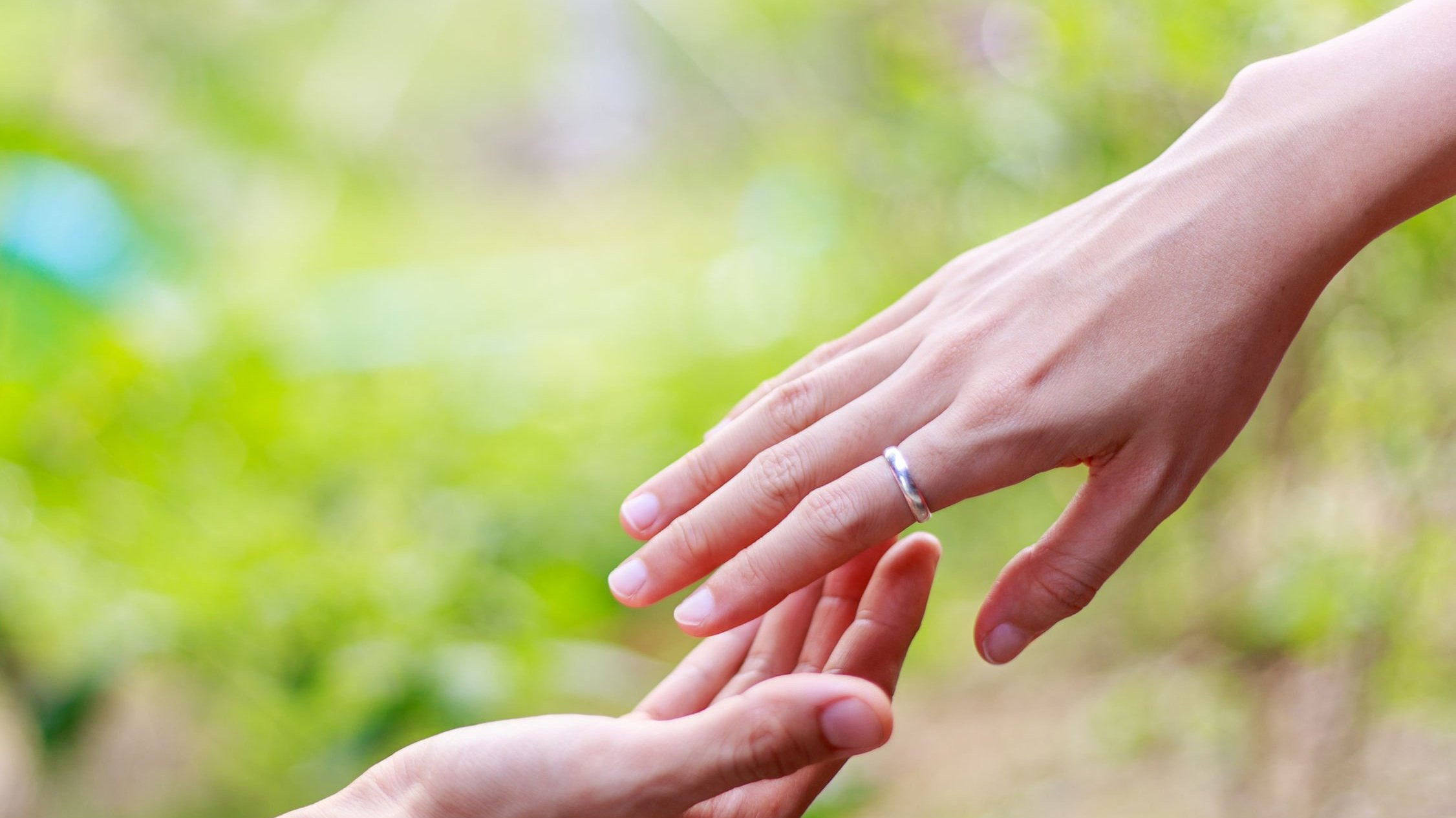 Mãos próximas uma da outra sobre cenário de folhas