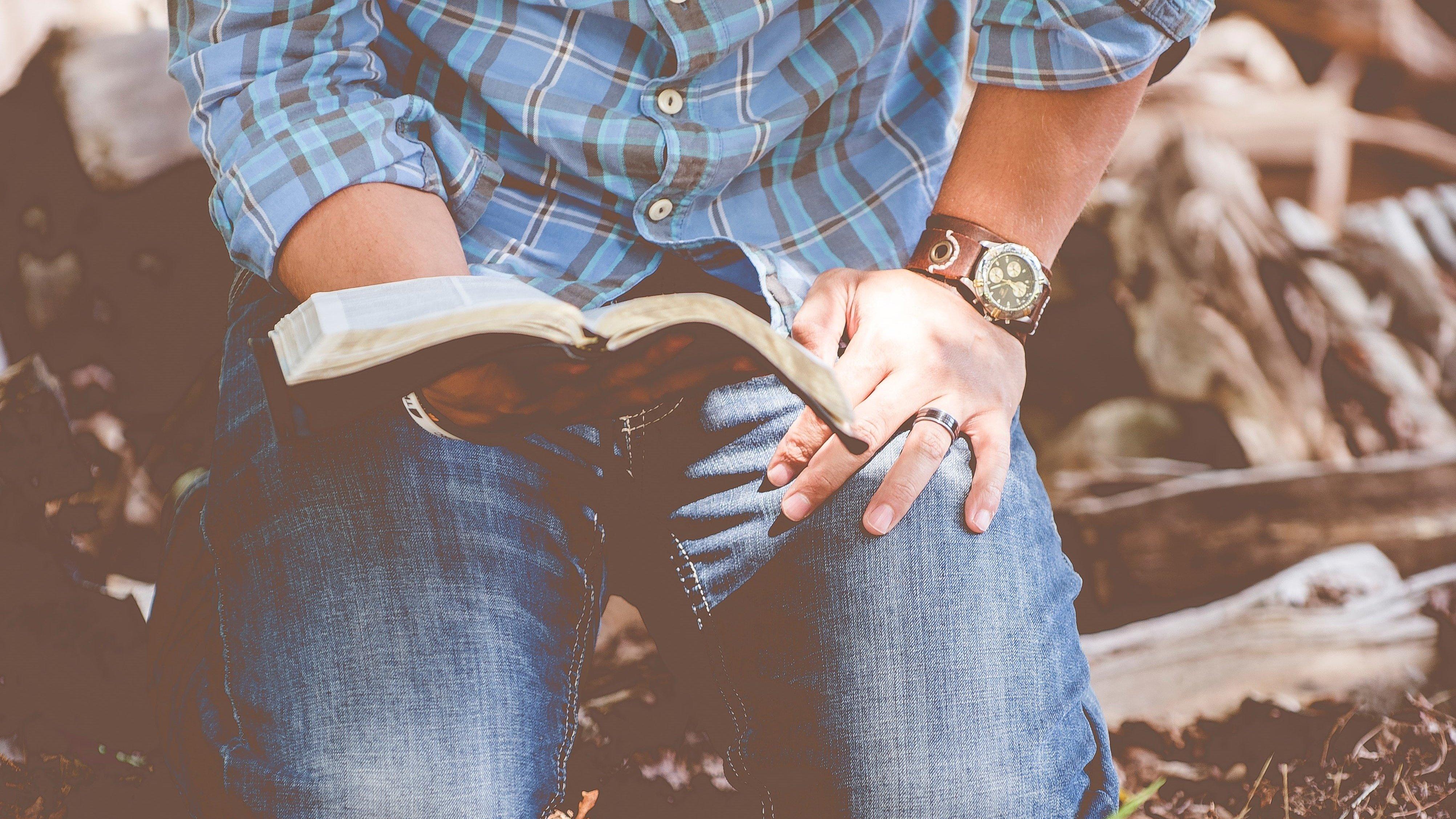 Homem ajoelhado na terra com uma bíblia na mão
