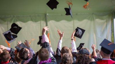 Imagem de pessoas em formatura jogando seus capelos para cima