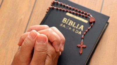 Uma Bíblia e uma caneca de café sobre uma mesa de madeira à beira de um rio.