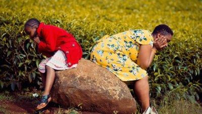 Menina e mulher sentadas em uma pedra, de costas uma para a outra. Ambas com o rosto apoiado nas mãos, e os cotovelos apoiados nas pernas.