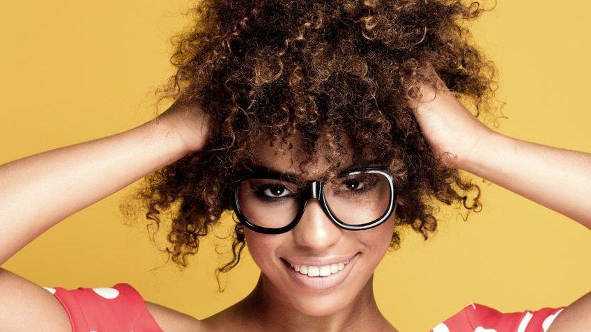 Garota com as mãos no cabelo cacheado usando óculos e o fundo amarelo