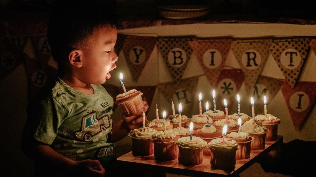 Menino em frente de muitos cupcakes, com uma vela no topo de cada. Ele segura um dos cupcakes com a vela acesa, e o leva em direção a sua boca.