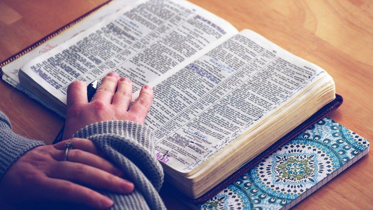 foto de pessoa lendo a bíblia enquanto segura caneta