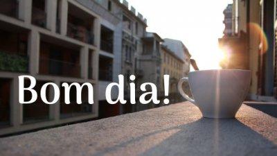 Imagem de xícara de café na janela com sol nascendo e escrito: Bom dia!