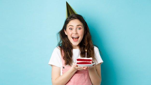 Mulher segurando balões de aniversário.