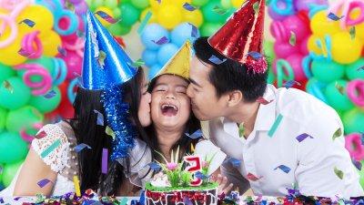 Mulher e homem beijam a bochecha da filha, em frente a um bolo enfeitado e uma vela com o número cinco.