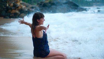 Mulher de maiô ajoelhada na água do mar na praia, com os braços abertos.