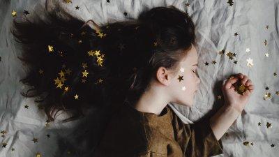 Mulher deitada na cama com estrelas no cabelo, no rosto e na cama